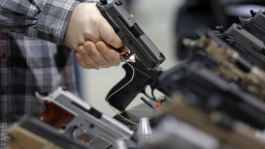 Image: A visitor holds a pistol at a gun display during a National Rifle As