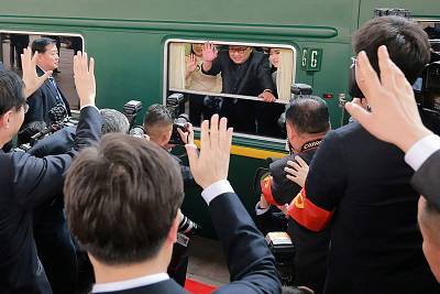 Kim Jong Un waves from his train as it leaves Beijing.
