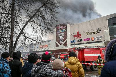 Residents watch the fire at the Zimnaya Vishnya shopping center in the Siberian city of Kemerovo, Russia, on Sunday.