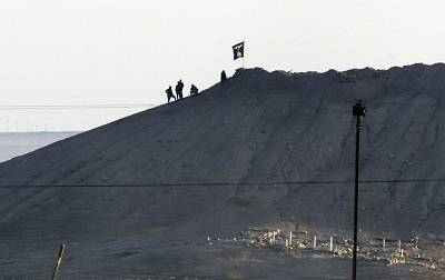 Islamic State militants place their group\'s flag on a hilltop in Kobani, Syria, in 2014.