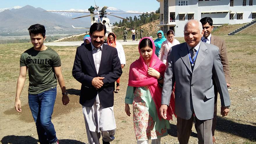 Image: Malala Yousafzai walks with her father, Ziauddin (2L), brother Atal