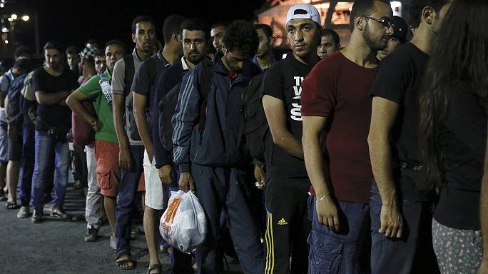 Syria refugees begin boarding Greek passenger ship in Kos