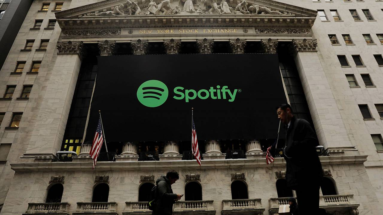 Image: Pedestrians walk past a Spotify banner on New York Stock Exchange