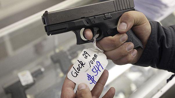 Image: A customer looks at a Glock 29 10mm hand gun at the Guns-R-Us gun sh