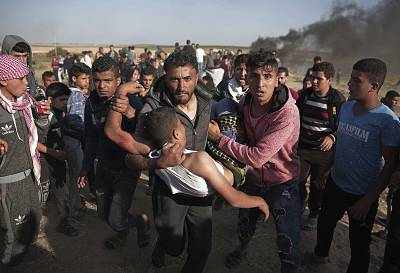 Palestinian protesters carry a wounded man who was shot by Israeli troops last week.