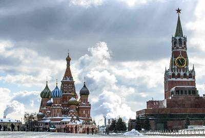 People walk in front of St. Basil\'s Cathedral and the Kremlin on Red Square in Moscow on March 16, 2018.