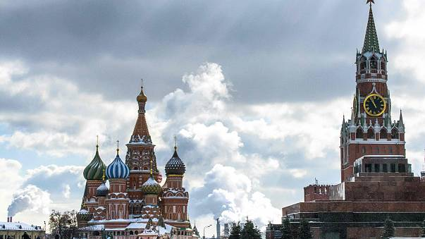 Image: People walk in front of St. Basil's Cathedral and the Kremlin on Red