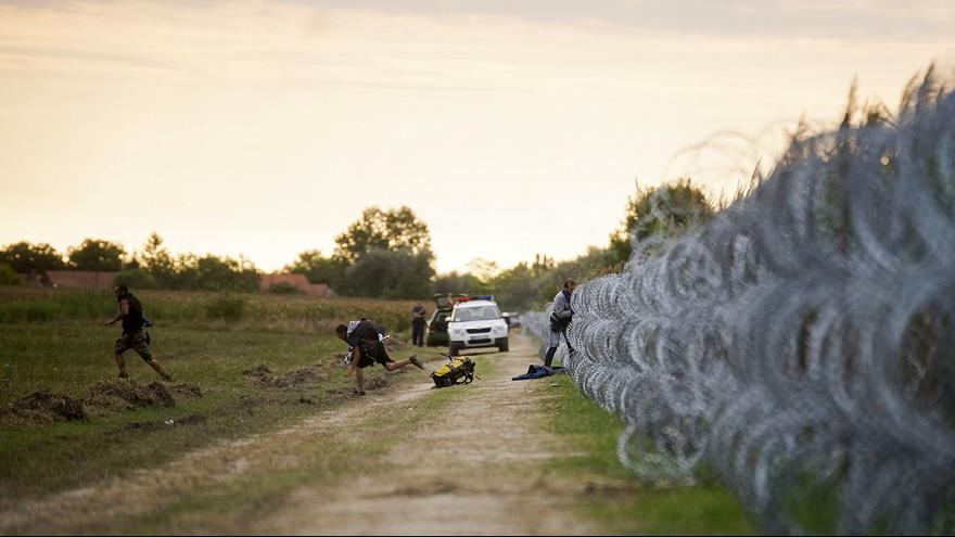 Trouble on Hungary's border escalates as migrants fight tear gas to beat fence
