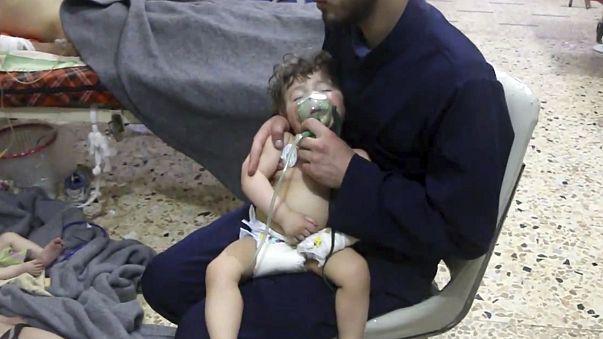 Image: A medical worker giving a toddler oxygen through a respirator