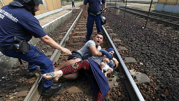Migrants pulled from train tracks by Hungarian police