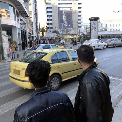 Khasim, right and his friend Fazul, left, look toward the yellow phone booths in the northwest corner of Omonia Square in Athens.