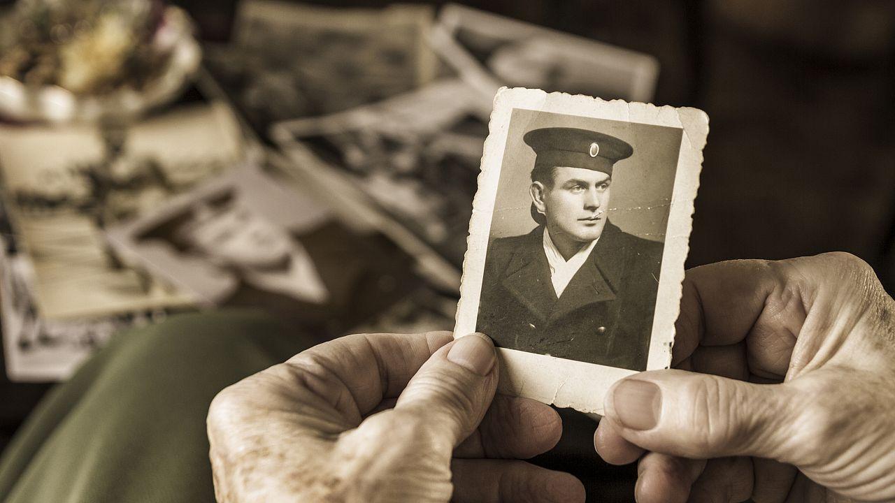 Senior woman holding dear photograph of her husband