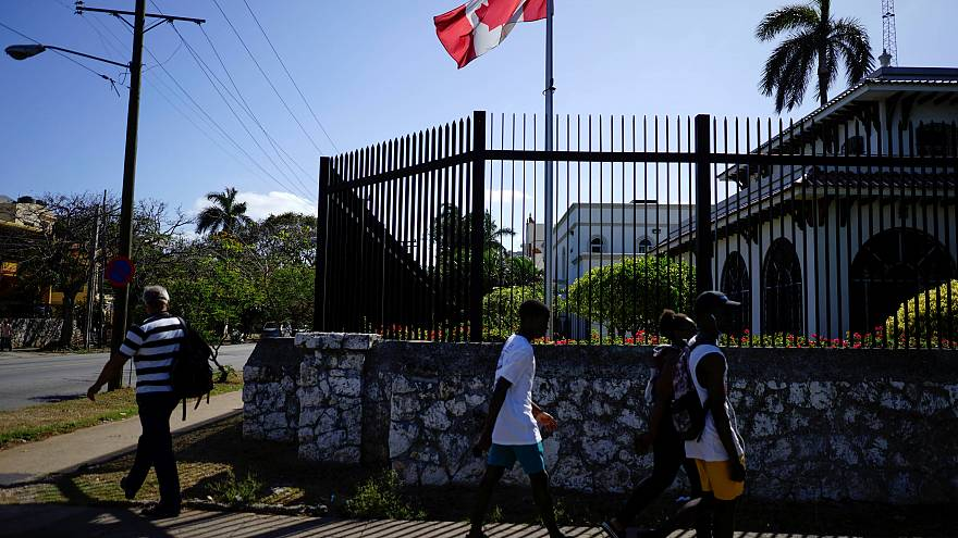 Image: People pass by the Canada's Embassy in Havana