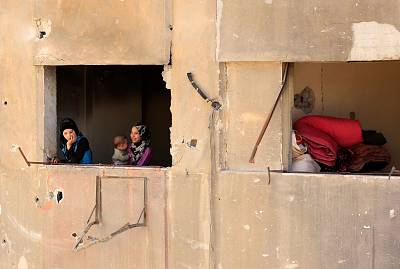Syrians look out of the window of a damaged building in Douma.