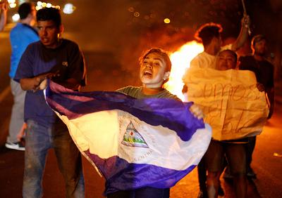 A demonstrator holds a Nicaraguna flag next to a burning barricade during demonstrations Saturday in Managua, Nicaragua.