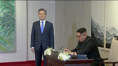 North Korean leader Kim Jong Un signs a guest book as South Korean President Moon Jae-in looks on at the inter-Korean summit in Panmunjom on Friday.