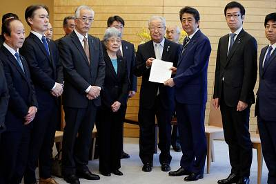 Japan\'s Prime Minister Shinzo Abe receives a petition from Shigeo Iizuka (center), who is the leader of a group of families of Japanese nationals abducted by North Korea.