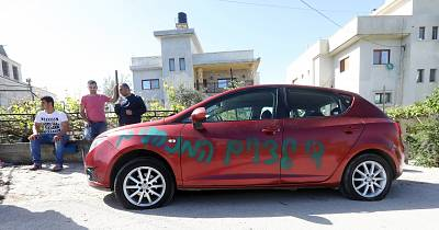 "A Palestinian car with slashed tires is covered with graffiti in Hebrew reading ""price tag"" in West Bank village of Farata on April 4."