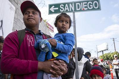 "Central American migrants travelling in the ""Migrant Via Crucis"" caravan wait outside the Padre Chava\'s kitchen soup for breakfast and legal counseling, in Tijuana, Baja California State, Mexico on April 27, 2018."