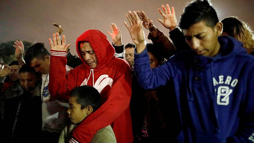 Image: Members of a caravan of migrants from Central America, pray near the