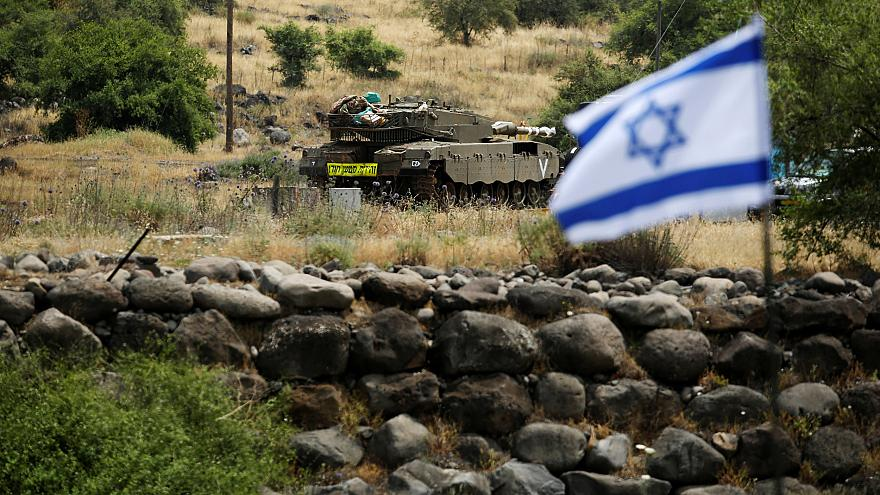 Image: An Israeli tank can be seen near the Israeli side of the border with