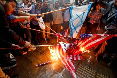 Iranians burn U.S. flags and makeshift Israeli flags on Wednesday.