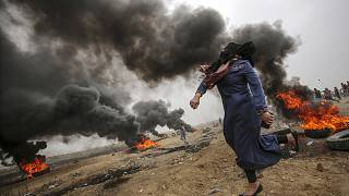 Image: A female Palestinian protester throws stones during clashes