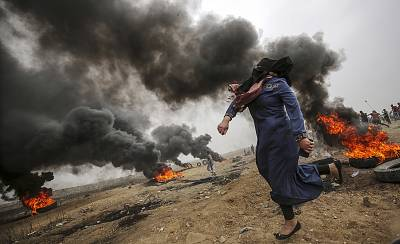 A female Palestinian protester throws stones during clashes in eastern Gaza City on May 4.