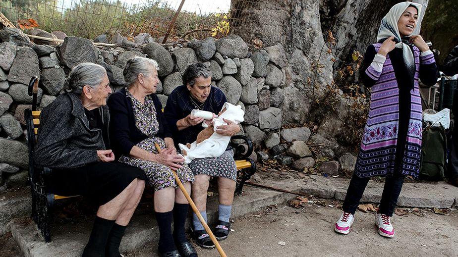 Trois vieilles femmes grecques prennent soin d'un bébé migrant à Lesbos