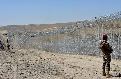 A Pakistani army soldier stands guard along with border fence.