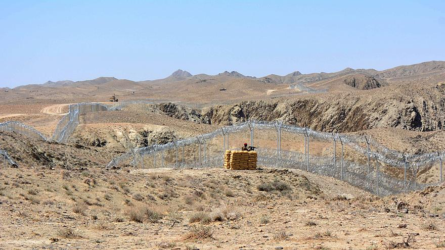 Image: A Pakistani army soldier stands guard along with border fence with A