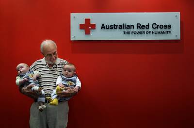 Harrison with twin boys Seth and Ethan Murray in the Apheresis department at the Australian Red Cross Blood Service. Hundreds of thousands of babies owe their health, and in some cases their life, to Harrison.
