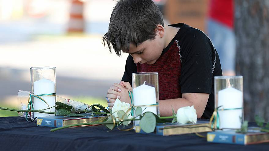 Image: A young boy prays during a vigil held at the Texas First Bank after