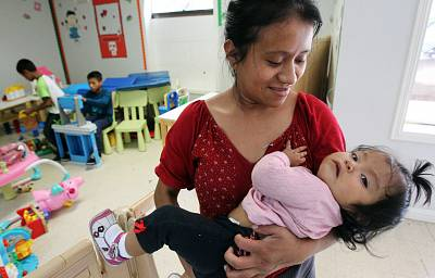 Carmelina Beatríz Tomás Jesús, 23, of Guatemala holds her 10-month-old daughter, Guadalupe Marley, while waiting at the Catholic Charities Rio Grande Valley Respite Center.