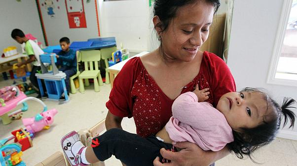 Image: A mother holder her daughter at a shelter