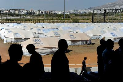 Migrants stand in front of tents at the former Olympic baseball complex in Athens in May 2016.