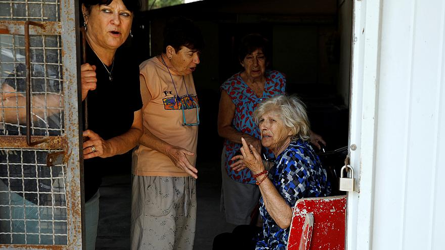 Image: Women react after a siren is sounded, in a Kibbutz on the Israeli si