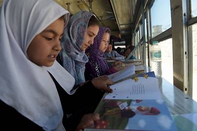 Afghan children read books in a mobile library bus in Kabul, April 4, 2018.