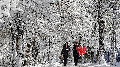 Women walk along snow-covered alley in Almaty