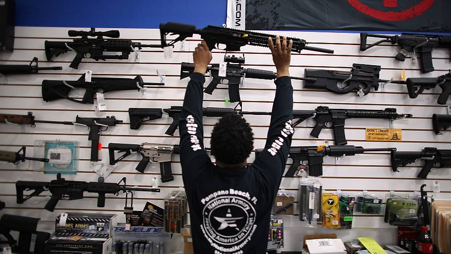 Image: Mike Acevedo Puts a Weapon on Display at the National Armory gun sto