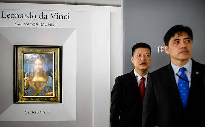 A man (right, wearing blue tie) identified by Hong Kong media as former CIA agent Jerry Chun Shing Lee stands in front of a member of security at the unveiling of a Leonardo da Vinci\'s painting at the Christie\'s showroom in Hong Kong.