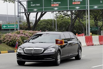 North Korean leader Kim Jong-un is driven in car with flags flying as the motorcade heads out of Singapore Airport on Sunday.