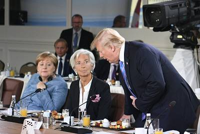 German Chancellor Angela Merkel and International Monetary Fund Managing Director Christine Lagarde react as President Donald Trump arrives late for a breakfast meeting discussion on gender equality at the G-7 summit on Saturday.