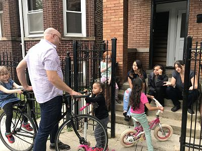 Pete DeMay and Liz Gres help Perla and Skarleth learn how to ride scooters and bicycles alongside their own children, Maggie and Anthony, in Chicago.