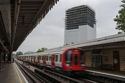 A subway train passes through a station near the burned-out shell of Grenfell Tower in May.
