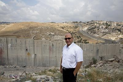Anwar Bader in front of the Israel separation wall in Abu Dis and an olive grove belonging to his family that they can no longer visit because of the barrier.