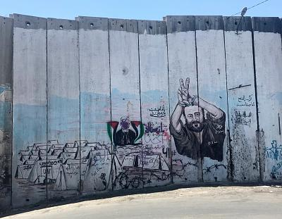 A portrait of Marwan Barghouti, in jail serving five life sentences for murdering Israelis, flashing a victory symbol with his raised handcuffed hands on the separation wall between Israel and the West Bank in Abu Dis. To the left is a defaced portrait of Mahmoud Abbas, the leader of the Palestinian Authority.