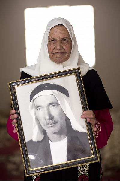 Hamamh El Jafal, 80, holds a photograph of her father, Ahmed Salem Jafal, who she says encouraged her love of farming.