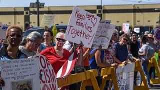 Image: Protesters hold signs in front of a Homeland Security facility in El