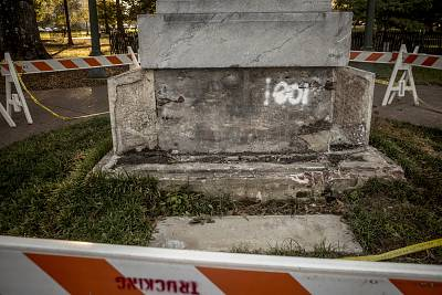 Barricades surround a damaged monument to Confederate soldiers.